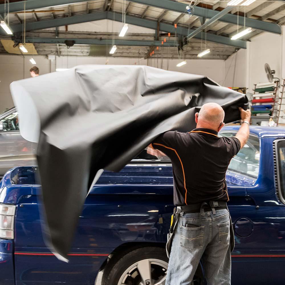 Douglas Innovation team fitting a custom made tonneau cover to a ute